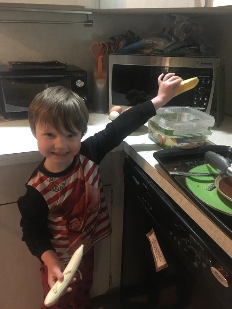 Ethan putting banana peel in compost bucket.
